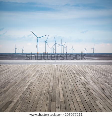 wind farm in mud flat with wooden floor ,develop shoals and renewable energy concept. - stock photo