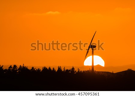 Wind farm in New Zealand with the sun  rising up.