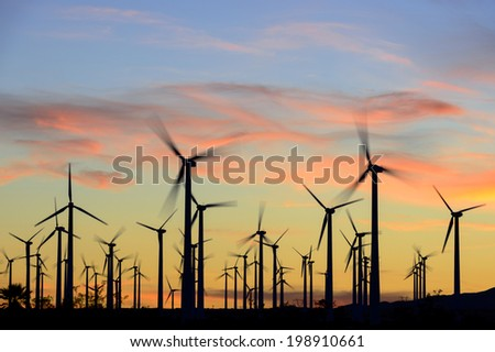 Wind farm in silhouette at dusk - stock photo