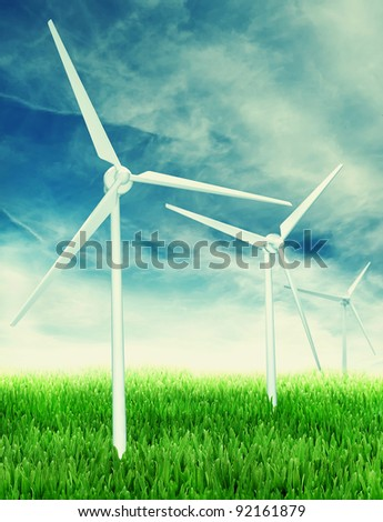 Wind farm: Industrial Eolic installation in a green field of grass - stock photo