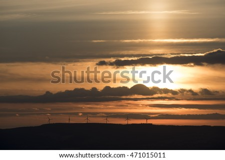 Wind farm on a hill in backlight at sunset