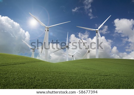 Wind farm producing clean renewable energy in front of a  blue sky and bright sun - stock photo