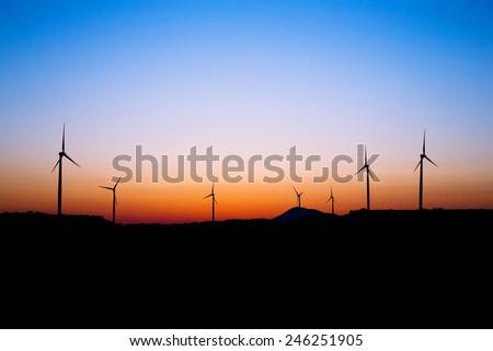 Wind farm silhouette in sunset light. Windmills. - stock photo