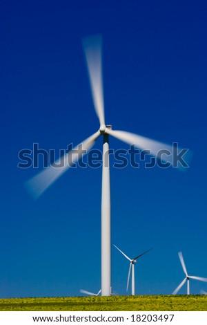 Wind farm turbines in green field over blue sky - stock photo