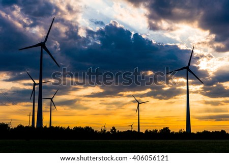 Wind farm using renewable energy source the wind and produces electricity in beautiful orange cloudy sunset over field