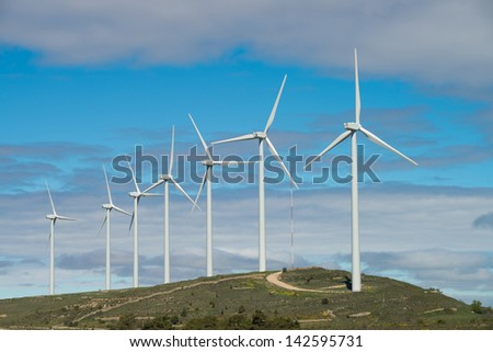 Wind farm with several generators on a hilltop - stock photo