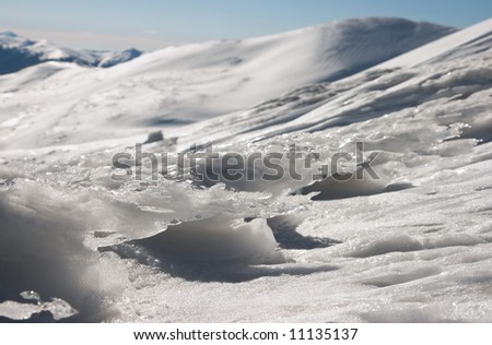 Wind form ice lumps on mountain landscape background (Ukraine, Carpathian Mt's, Stara and Petros mount behind (not in focus))
