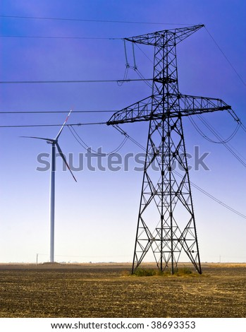 Wind generator and high-voltage tower in the field.