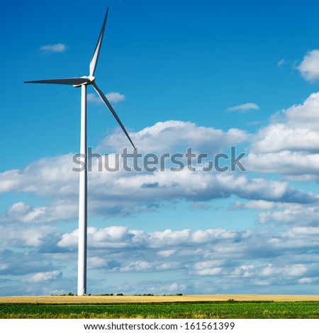 Wind generator turbine on summer landscape - stock photo