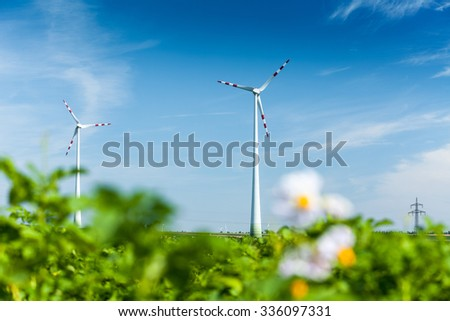 Wind generators in the green field at sunny day - stock photo