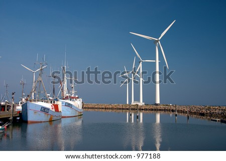 wind mills and fisher boats in a little danish harbour wind mill in denmark a sunny summer day (danish east coast) - stock photo