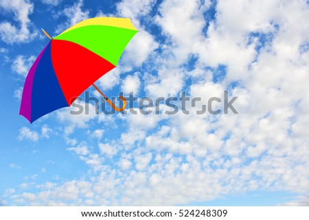 Wind of change concept.Multicolored umbrella flies in sky against of pure white clouds.Mary Poppins Umbrella.