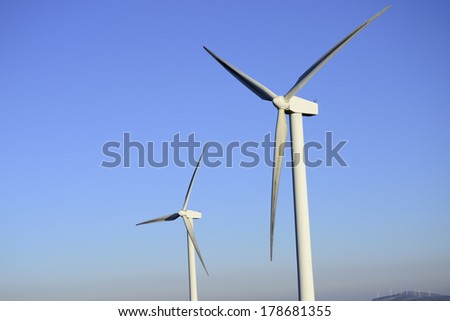Wind power and energy business. Turbines closeup with blue sky - stock photo