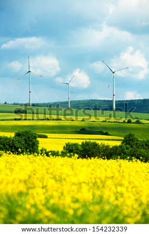 Wind power electricity turbines and field with green grass and yellow flowers stripes landscape