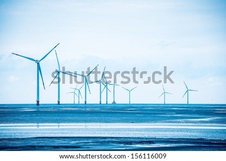 wind power farm in coastal mud flat,develop shoals concept. - stock photo