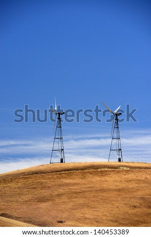 wind power farm on grass hill with blue sky