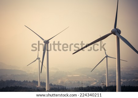 wind power generation turbine closeup at dusk in fog and haze   - stock photo