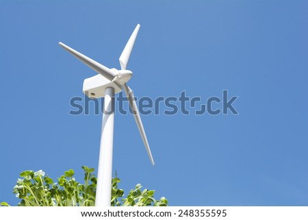 Wind power generator model and sprouts under blue sky - stock photo