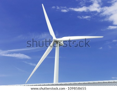 Wind power generator near the cottage roof - stock photo