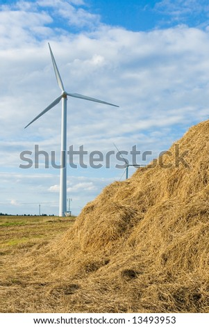 Wind power installation and pole high volts with blue sky - stock photo