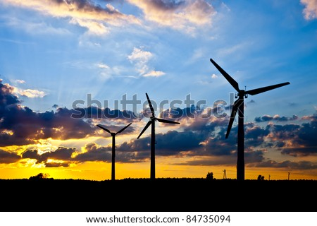 Wind power landscape at sunset. - stock photo