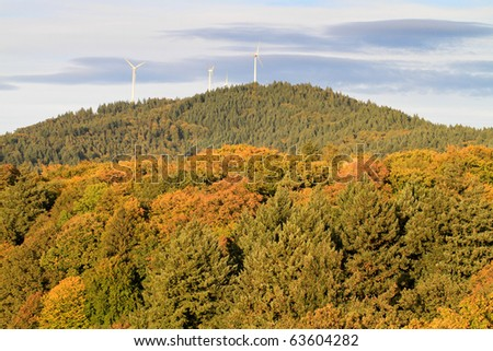 wind power mills in forest - stock photo