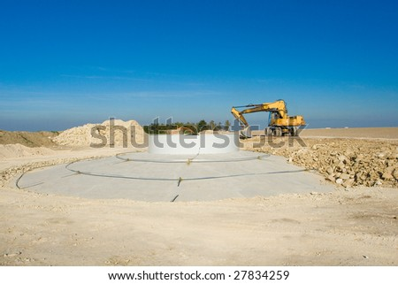 Wind power plant construction and yellow bulldozer - stock photo