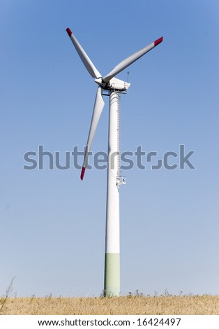 Wind power plant in front of a blue sky