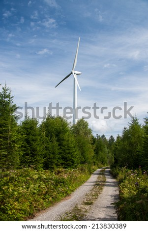 wind power plant in the forest - stock photo