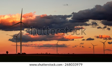 Wind power plant silhouettes in orange sunset - stock photo