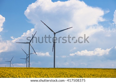 Wind power station at the yellow field - stock photo