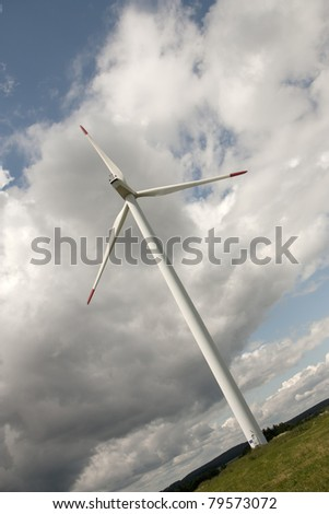 Wind power station in the country over cloudy sky - stock photo