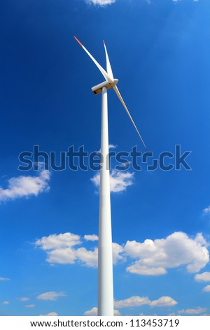 Wind power station wind turbine against clear blue sky and small clouds - stock photo
