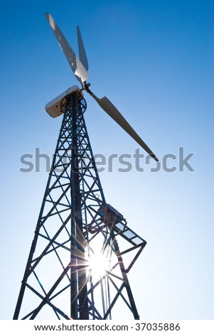 Wind power station - wind turbine against the blue sky - stock photo