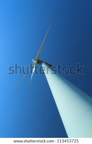 Wind power station with wind turbine as alternative energy source against clear blue sky vertical orientation - stock photo