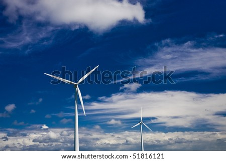 Wind power turbines on a blue and cloudy sky. - stock photo