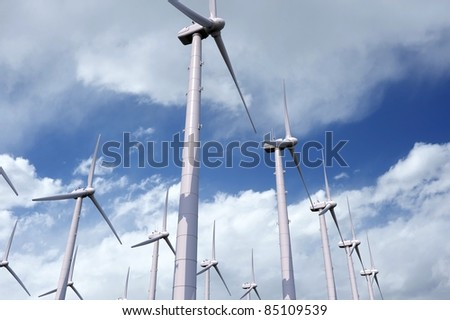 Wind Power - Wind Turbines Plantation on Blue Cloudy Sky. Green Energy Theme - Illustration / 3D Render - stock photo