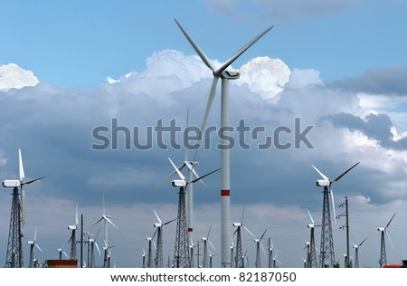 Wind-powered generators against clouds and blue sky - stock photo