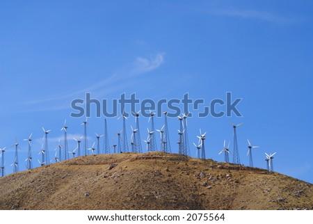 Wind powered generators dot the windy mountain passes - stock photo