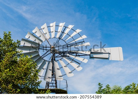 Wind powered multi-bladed water pump built in a German factory and since 1922 working as a water mill in a Dutch polder area. - stock photo