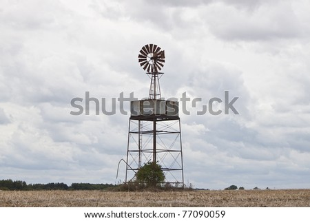 wind powered water pump in a field - stock photo
