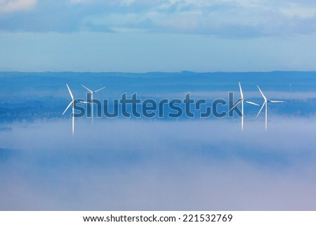 Wind powers in misty countryside landscape - stock photo