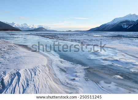 Wind sculpted snow patterns and frozen river ice on the Chilkat river near Haines Alaska on a sunny day. - stock photo