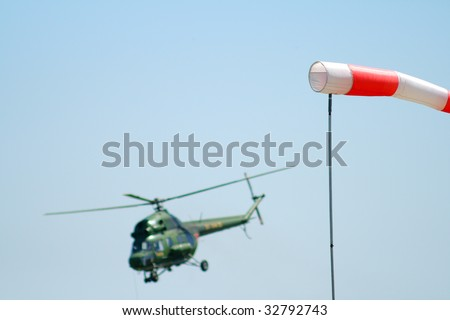 wind sleeve flying against the background of the helicopter - stock photo