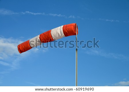 Wind sock in front of blue sky - stock photo