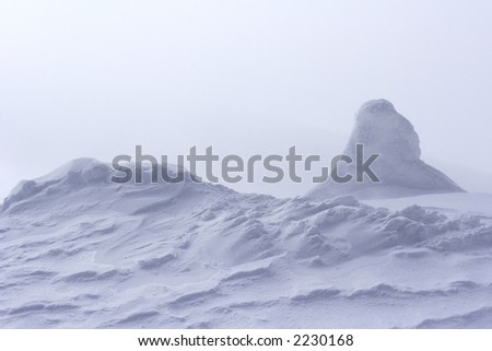 wind swept snow drift at top of mountain - stock photo
