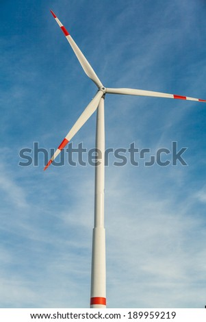 Wind turbine against a blue hazy sky in a conceptual image of renewable and alternative energy resources to save the environment