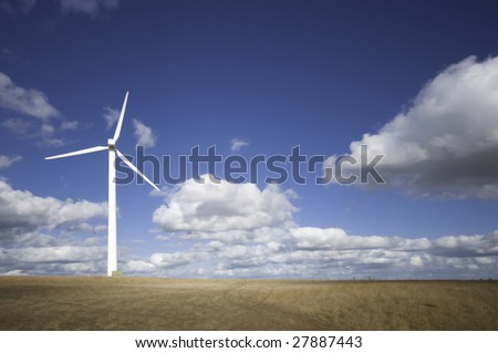 Wind turbine against a sky blue background with clouds. Part of a series - stock photo