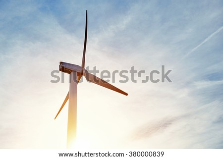 Wind turbine against beautiful cloudy sky and sun rays, electric generator outside the city, windmill standing with sunset on background,  alternative energy resources - stock photo
