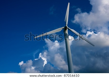 Wind turbine against blue sky.